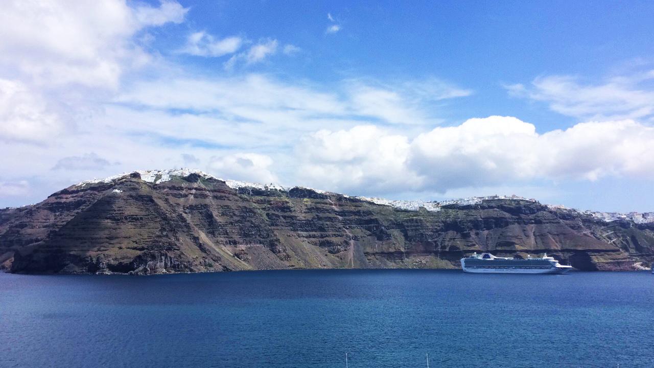 kruzer Santorini Grčka plavo nebo morska obala otok